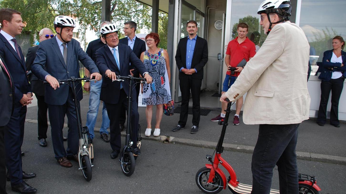 Metz-Geschäftsführer Wilhelm Daum (rechts) stellt NRW-Ministerpräsident Armin Laschet (Dritter von links) und Bundeslandwirtschaftsminister Christian Schmidt (Zweiter von links) den neuen Elektroroller vor.