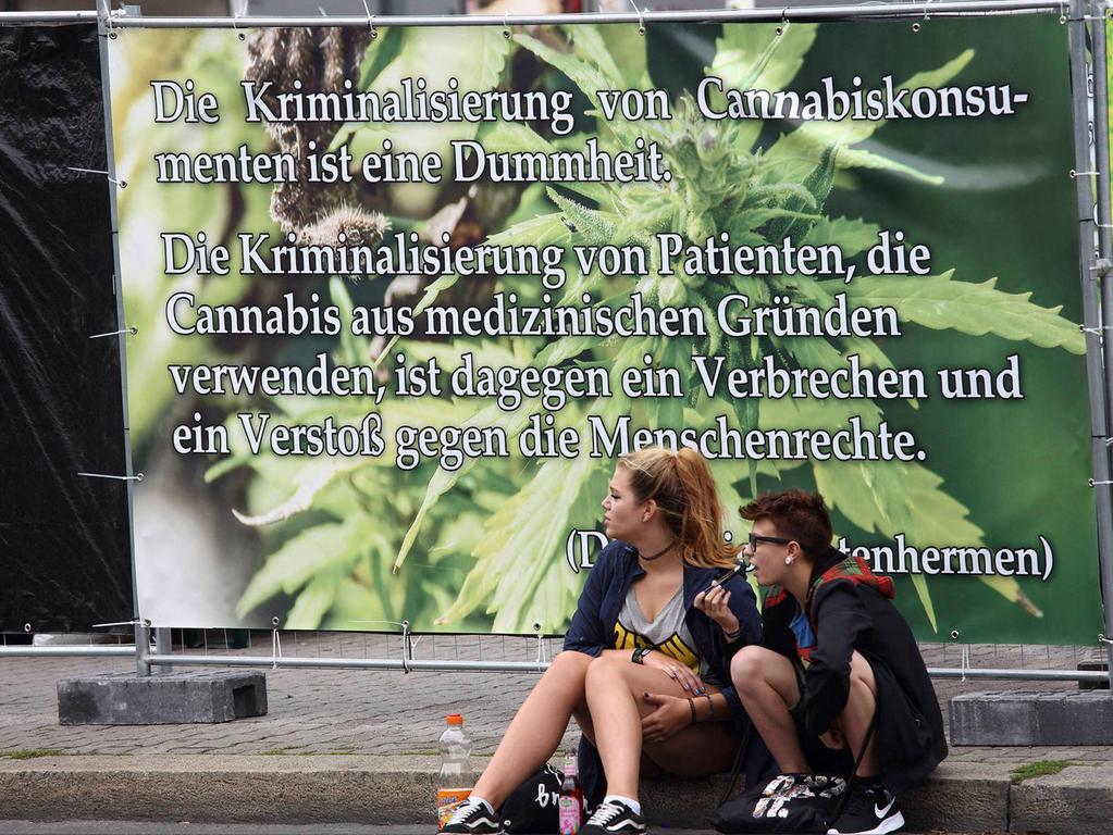 Jugendliche sitzen vor einem Transparent zur Legalisierung von Cannabis bei der Hanfparade am 12.08.2017 in Berlin. Fuer einige kranke Menschen in Deutschland war der 18. Januar 2017 ein Tag grosser Hoffnung: Damals beschloss der Bundestag, medizinisches Cannabis auf Kassenrezept verfuegbar zu machen. Auch die Kostenuebernahme durch die gesetzlichen Krankenkassen wurde vorgesehen. Das neue Gesetz ist zwar bereits im Maerz in Kraft getreten, aber es gibt immer noch viele Unklarheiten - vor allem aber jede Menge Wut und Enttaeuschung auf Patientenseite. (Siehe epd-Bericht vom 28.08.17)