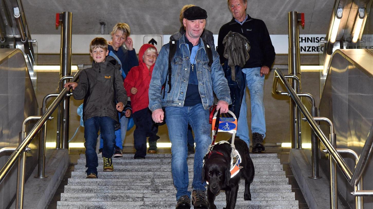 Mit Hund und Geschirr geht es vorsichtig die Treppe im U-Bahn-Geschoss hinunter. Die Gruppe schaut gespannt zu.