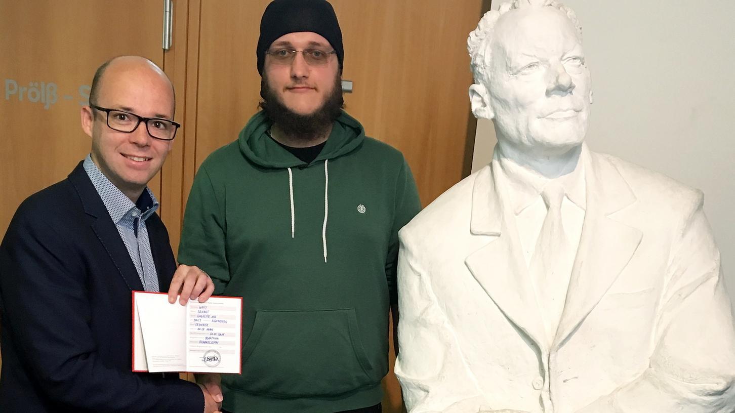 SPD-Chef Thorsten Brehm (l) überreicht dem 23-jährigen Willy Brandt das Parteibuch der SPD.