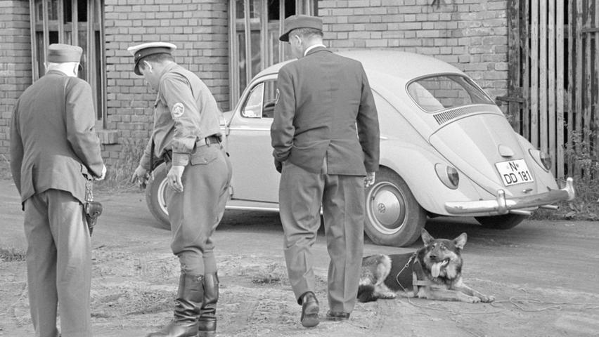 Polizeibeamte sichern die Fußspuren des Täters. Im Hintergrund der Wagen, den der Räuber an der alten Ziegelei in Boxdorf abgestellt hat. Von hier flüchtete er zu Fuß weiter.  Hier geht es zum Kalenderblatt vom 01.Oktober 1967: Jagd auf Autoräuber