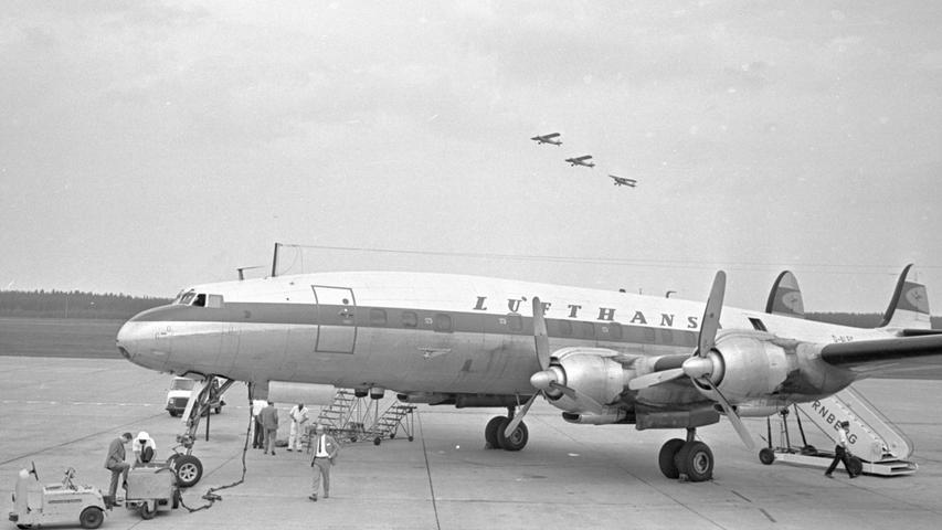 Wie an einer Schnur aufgereiht fliegt die Burda-Staffel über den Platz, auf dem eine Super-Constellation (vorne) der Lufthansa startbereit für die Rundflüge steht. Hier geht es zum Kalenderblatt vom 01.Oktober 1967: Jagd auf Autoräuber