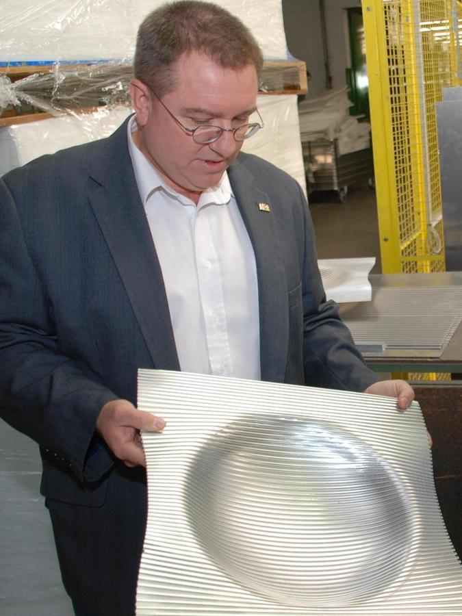 Vertriebsleiter Oliver Schmitz zeigt eine Obstschale aus Aluminium, die einen Designpreis gewonnen hat.