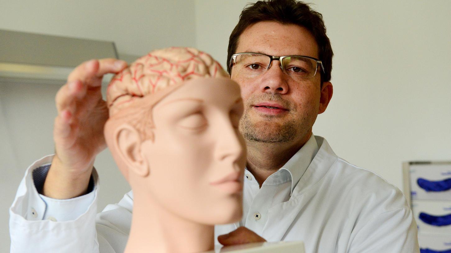 Prof. Dr. Christian Maihöfner, Leiter der Neurologie am Klinikum Fürth, erläutert am Gehirnmodell Auslöser eines Schlaganfalls.