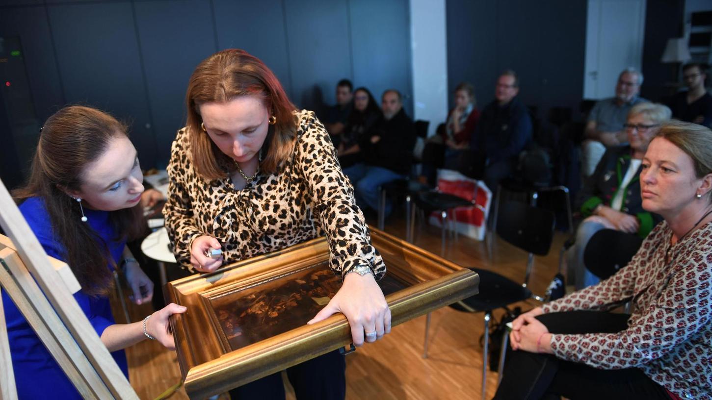 Kerstin (links) und Kathrin Weidler nehmen ein altes Gemälde unter die Lupe. Das Publikum verfolgt aufmerksam die öffentliche Untersuchung.
