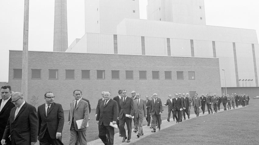 Ein eindrucksvolles Werk der Technik: Die Ehrengäste in feierlich dunklen Gewändern ziehen am mächtigen Kesselhaus vorbei, das 70 Meter hoch aufragt und mit seiner formschönen Aluminiumverkleidung besticht.  Hier geht es zum Kalenderblatt vom 23. Oktober 1967: Starke Stromquelle