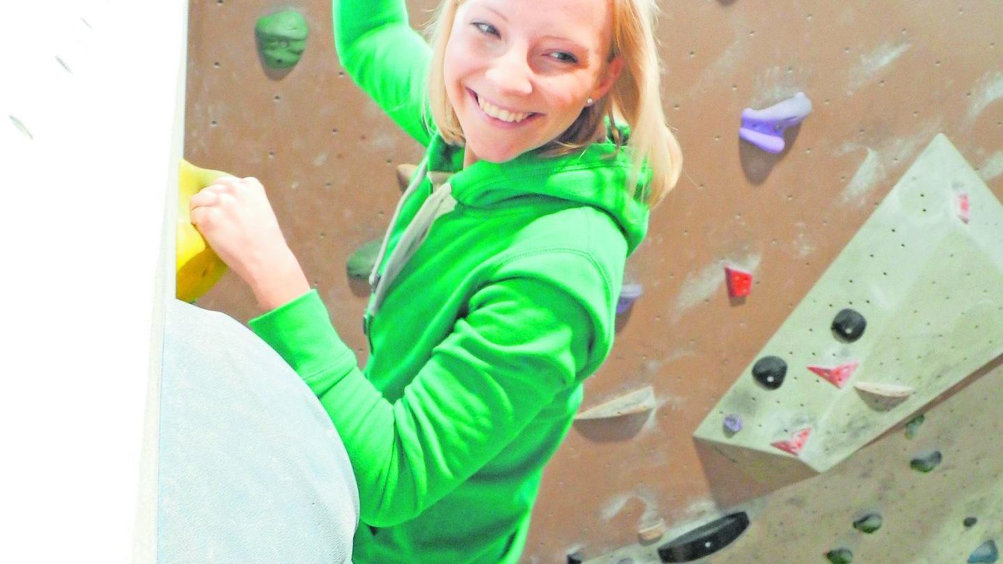 Therapeutin Carolin Sack klettert an der Boulderwand voran — die Kolleginnen feuern sie an.