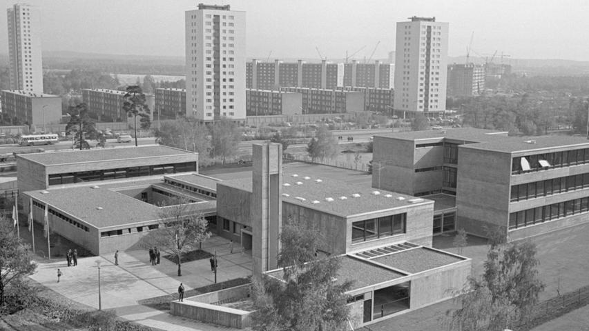 Der ausladende Schulkomplex im Vordergrund wirkt geradezu zierlich angesichts der Wohntürme von Neuselsbrunn (jenseits der Münchener Straße im Hintergrund) und dem Hochhaus der Zollhaus-Wohnanlage (rechts) und hat dennoch viel Platz und Bedeutung. Zu dem dreigeschossigen Klassentrakt fügen sich Pausenhalle, der Jugendhort und die Turnhalle (links) sowie die Hausmeisterwohnung (rechts).  Hier geht es zum Kalenderblatt vom 27. Oktober 1967: Kinder zwischen Wolkenkratzern