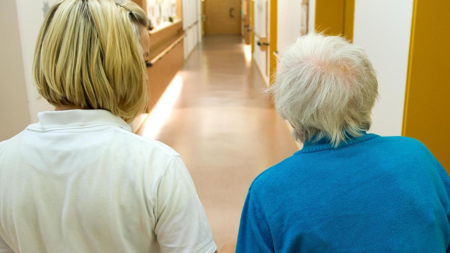 Eine an Demenz erkrankte Frau wird von einer Pflegeschülerin über den wenig anheimelnden Flur eines Pflegeheims geführt.