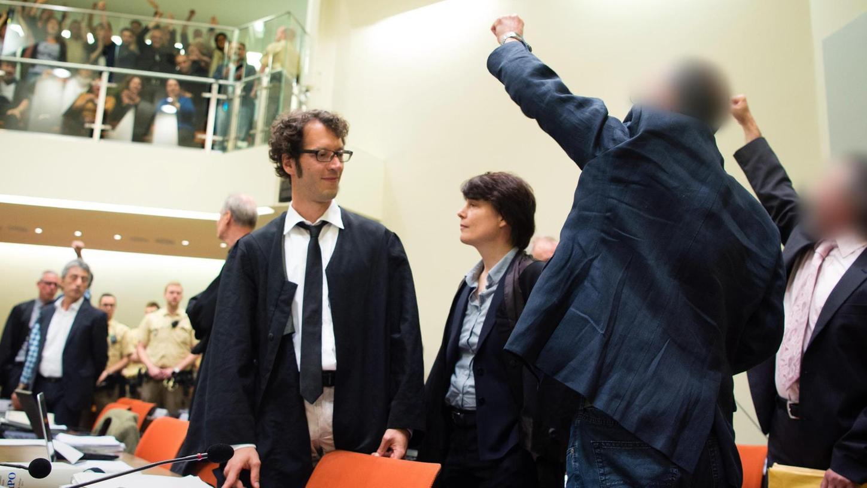 Zwei Angeklagte grüßen hoch zur Zuschauertribüne. Es ist ein quälend langsamer Prozessverlauf. Seit eineinhalb Jahren wird vor dem Oberlandesgericht München verhandelt. Der Prozess gilt als Pilotverfahren, in dem der juristische Umgang mit der TKP/ML geklärt werden soll.