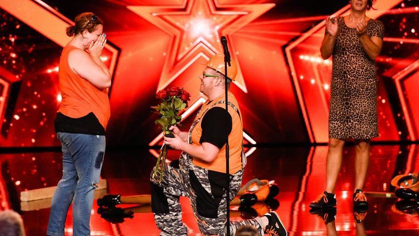 Ganz orange mit einem Blumenstrauß: Christian Rümler kniet vor seiner Michaela.