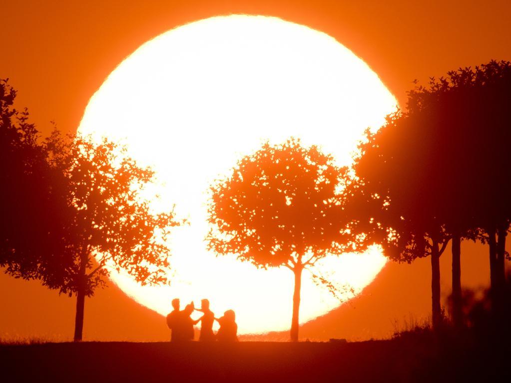 dpatopbilder Menschen stehen am 12.09.2016 am Kronsberg bei Hannover (Niedersachsen), als am Horizont die Sonne untergeht. Der September bleibt sonnig: Für Teile Deutschlands gab der Deutsche Wetterdienst (DWD) sogar eine Hitzewarnung aus. Foto: Julian Stratenschulte/dpa +++(c) dpa - Bildfunk+++ |