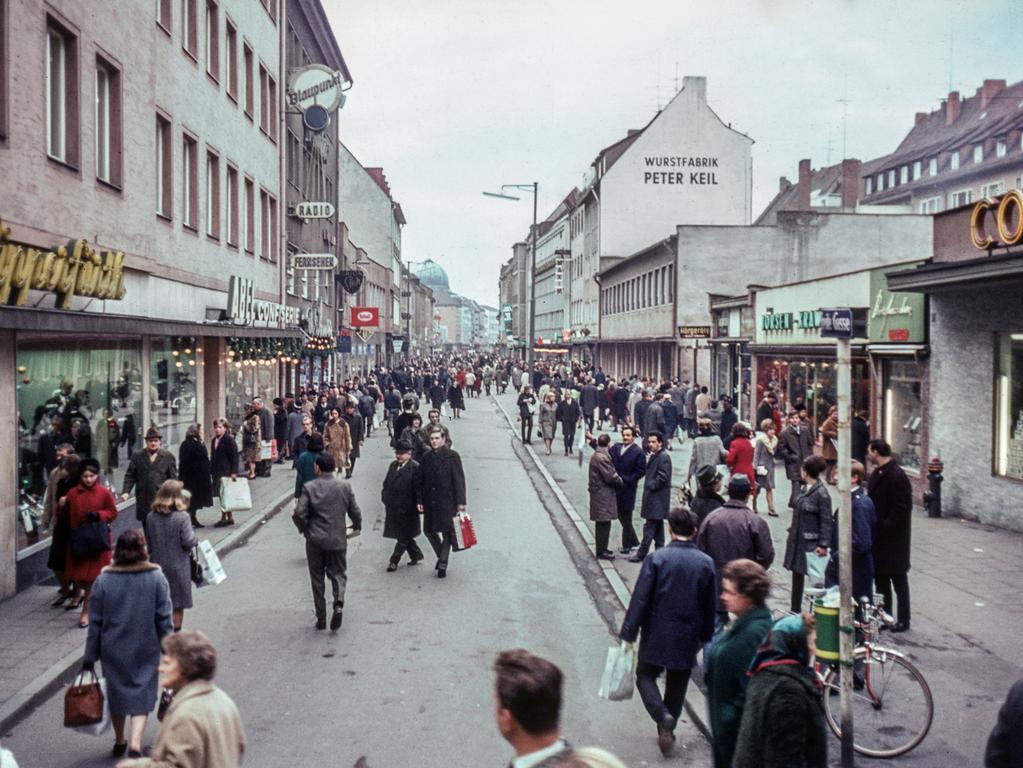 MOTIV: Nürnberg, historisch; Stadtansicht; 1960er Hier: Nach zum Teil heftigen Widerständen wurde 1966 in einer Probephase die  Breite Gasse zur autofreien Zone umfunktioniert. Da dieser Schritt von der  Nürnberger Bevölkerung gut angenommen wurde, konnten in der Folgezeit weitere  Fußgängerbereiche in der Altstadt etabliert werden. Nürnberg besitzt somit eine  der ältesten Fußgängerzonen in Deutschland. Verkehr; PKW; Vergleich jüngere  Ansicht / Vorher / Nachher - Bild. Dezember 1966. FOTO: Stadtarchiv Nürnberg, Sign. StadtAN A 55 Nr. I-7-2-10) Entnommen aus dem Buch