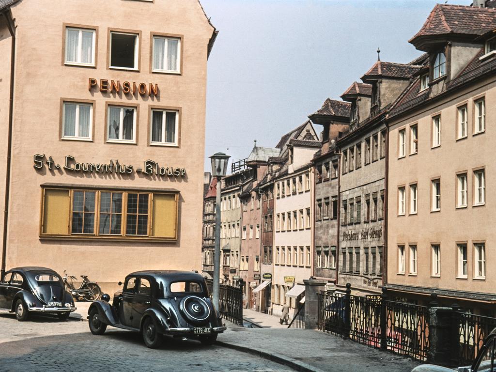 MOTIV: Nürnberg, historisch; Stadtansicht; 1950er. Hier: Der Blick von der Hinteren Ledergasse in die Obere Wörthstraße.  Außenansicht Pension St. Laurentius - Klause. Die geschlossene traufseitige  Bebauung und der Mercedes im Vordergrund erwecken den Eindruck, dass es sich  hier um eine Vorkriegsaufnahme handelt. Der VW-Käfer mit dem Ovalfenster, links  im Bild, wurde jedoch erst ab 1953 produziert. Nach 1953. Verkehr; PKW; VW  Käfer. FOTO: Hochbauamt / Stadtarchiv Nürnberg, Sign. StadtAN A 55 Nr. I-50-1-3 Entnommen aus dem Buch