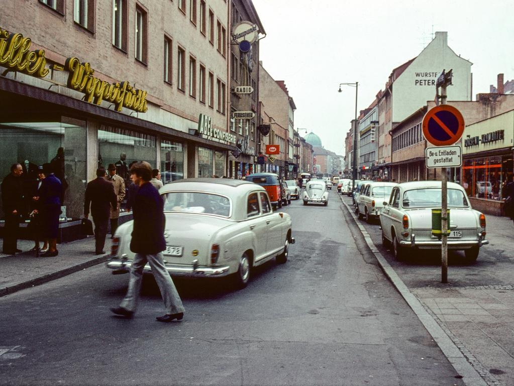 MOTIV: Nürnberg, historisch; Stadtansicht; 1960er Hier: Nach zum Teil heftigen Widerständen wurde 1966 in einer Probephase die  Breite Gasse zur autofreien Zone umfunktioniert. Da dieser Schritt von der  Nürnberger Bevölkerung gut angenommen wurde, konnten in der Folgezeit weitere  Fußgängerbereiche in der Altstadt etabliert werden. Nürnberg besitzt somit eine  der ältesten Fußgängerzonen in Deutschland. 1964. Verkehr; PKW; Vergleich  jüngere Ansicht / Vorher / Nachher - Bild. FOTO: Hochbauamt / Stadtarchiv Nürnberg, Sign. StadtAN A 55 Nr. I-7-1-6 Entnommen aus dem Buch