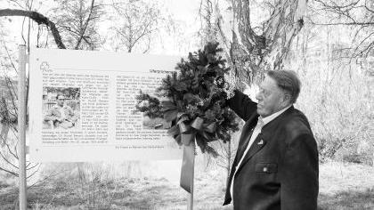 Nelken befestigt Seppl Schneider zur Erinnerung an seine einstigen Kameraden an der Erinnerungstafel bei den Birken am Ufer der Rednitz.