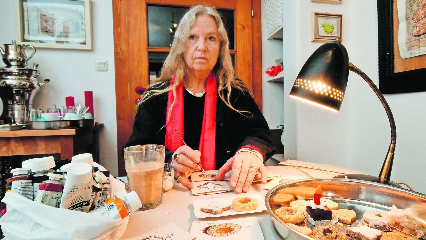 Sie malt konzentriert mit Acrylfarben auf historischen Dokumenten: Hier widmet sich Sabine Frank den Plätzchen, die ihr die Redakteurin vorbeigebracht hat. Noch bis morgen ist die Künstlerin im Ladenatelier Atzenhofer zu Gast.