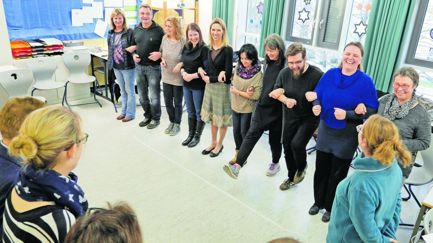 Claudia Böschel (violettes Oberteil) hakt sich bei den Lehrkräften ein. Bei dieser Übung werden Fragen beantwortet, dabei macht die Gruppe einen Schritt nach vorne oder nach hinten.