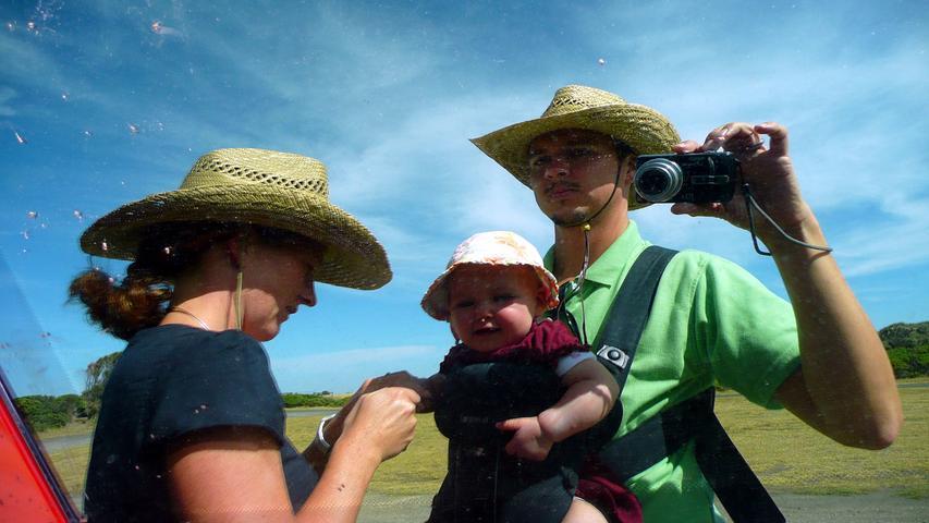 Die Familie spiegelt sich im Camper. Sonnenhüte sollte man sich in Australien unbedingt kaufen.