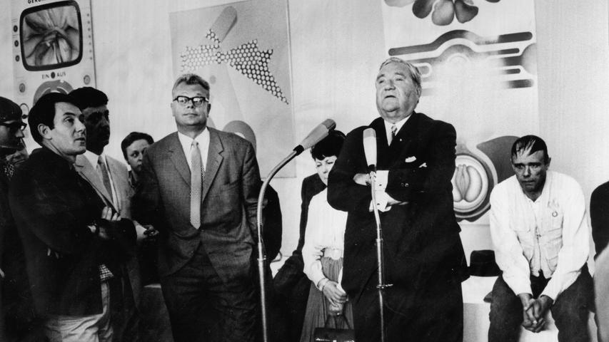 Dann eroberte die Kunst das Haus zurück. 1968 eröffnete die Künstlerbund-Ausstellung, die sich über die Kunsthalle und das Künstlerhaus erstreckte. Zur Eröffnung begrüßte Kulturreferent Hermann Glaser (mit Brille) Bundesratsminister Carlo Schmid (am Mikro) und den damals umstrittensten deutschen Künstler Joseph Beuys (sitzend). Der errichtete eine seiner berühmten Fettecken.