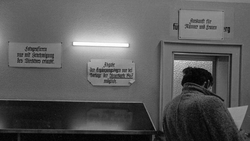 Mit hochgeschlagenem Mantelkragen wartet dieser Mann auf eine bessere Zukunft. Fotografieren ist in den Gängen des Arbeitsamtes nicht gestattet. Nur das Verbotsschild darf aufgenommen werden. Hier geht es zum Kalenderblatt vom 3. Januar 1969: Gereizte Atmosphäre