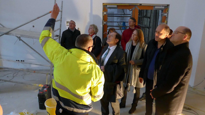 Architekt Ralf Glander erklärte Staatssekretär Füracker (r.) den Baufortschritt wofür Investor Falko Weber (2. v. r.) dessen Bewunderung galt. MdL Hans Herold (5. v. r.) galt das Lob seine hartnäckigen Impulse zu den Behördenverlagerungen.