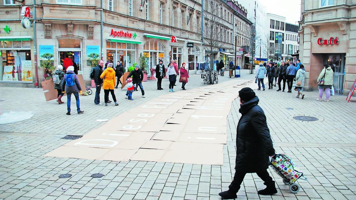 Aneinandergereihte Pappdeckel führten in der Fürther Fußgängerzone vor Augen, wie viel Fläche in Bayern binnen einer Minute im Durchschnitt versiegelt wird.