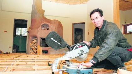 Selbst ist der Mann: Vor dem mächtigen Grundofen (im Hintergrund) sägt Alexander Mayer Latten und Dielenbretter für den Holzfußboden zu. Beton und Estrich sind im gesamten Haus Fehlanzeige.Foto: Mario Kreß