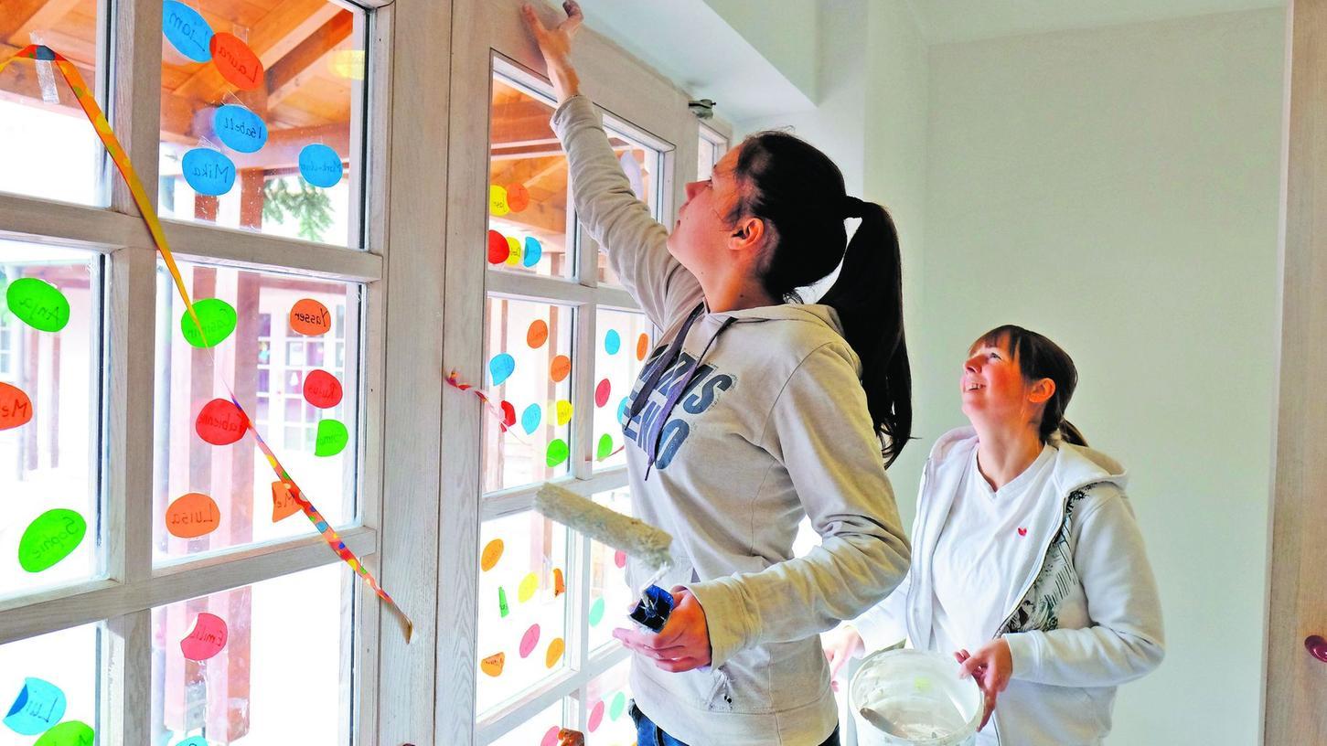 Unter der Aufsicht von Malermeisterin Angelika Drebinger (rechts) streichen die Schülerinnen und Schüler die Ganztagesräume des Liebfrauenhauses in frischem Weiß.