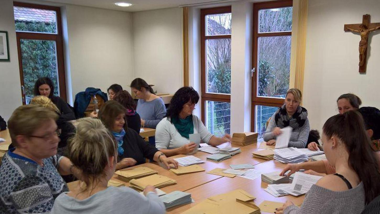 Unter großem Aufwand bereiten Helferinnen und Helfer in der Pfarrgemeinde St. Georg die Briefwahlunterlagen vor. Foto: Peter Schramm