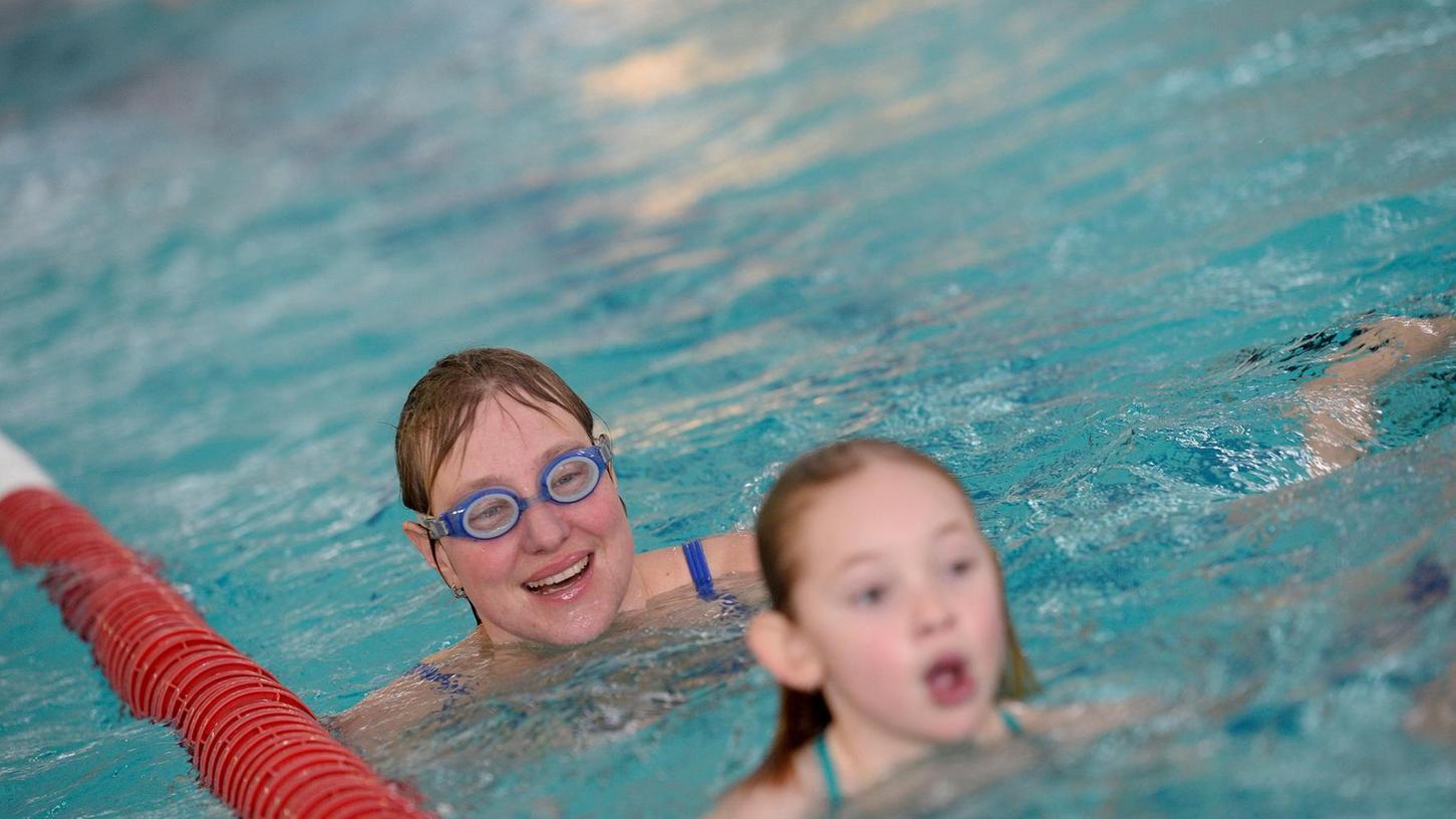 Frauen, Männer, Kinder, Sportgruppen und ganze Familien beteiligten sich am 24-Stunden-Schwimmen von DLRG/Delphin. Die Bahnenzähler hatten viel zu tun (rechts).