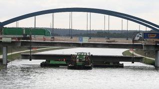 SCHWABACH - Millimeterarbeit war's am Samstagvormittag, bis das erste, rund 45 Meter lange Betonelement, das zuvor von der alten Autobahnbrücke über den Main-Donau-Kanal herausgesägt worden ist, abgelassen und sicher auf dem schwimmenden Ponton verladen war. Gezogen von einem Schlepper, wurde das etwa 470 Tonnen schwere Teil dann zur Schleuse Eibach gezogen. Dort, am befestigten Uferbereich, wird das Betonstück nun zerkleinert. Bereits am morgigen Dienstag, so schätzen die Bauexperten der Autobahndirektion, wird bereits das zweite Mittelstück der alten Brückenkonstruktion ebenso abtransportiert. Im Zuge des derzeit laufenden sechsstreifen Ausbaus der A-6-Fahrbahn Richtung Schwabach muss eine neue Brücke erstellt werden. Mitte des Jahres soll diese, genau wie ihr »Schwesterbauwerk» für die Fahrbahn Richtung Nürnberg im vergangenen Jahr, eingeschoben werden. Die neue Kanalbrücke kostet rund elf Millionen Euro.