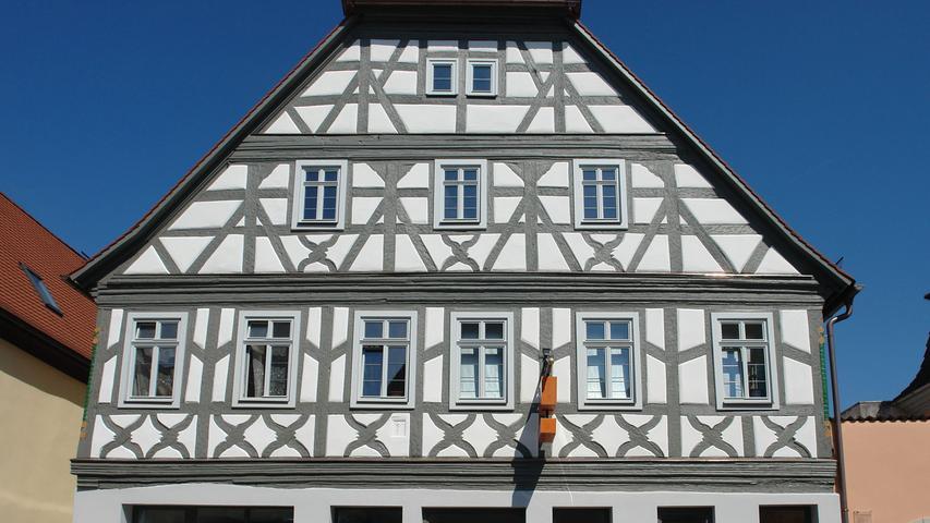 In Scheinfeld reihen sich entlang der beiden Seiten der Hauptstraße zumeist giebelständige und zweigeschossige, aber ansonsten unterschiedlich charakterisierte Häuser eng aneinander. Zu diesem variantenreichen Ensemble zählt auch das Wohnhaus Nr. 11, ein breit gelagerter Krüppelwalmdachbau aus dem 17. Jahrhundert. Sein zur Straße gerichteter Schaugiebel wird von Zierfachwerk geschmückt. Breit profilierte Gesimse setzen das Obergeschoss sowie die beiden Dachgeschosse ab, die Etagen werden mit Fachwerkelementen, u.a. einem Feuerbock, ausdifferenziert. Geschnitzte Eckpfosten im Obergeschoss – eine Art Blattstab, der zwei von Voluten eingefasste Weinreben verbindet – sind nochmals an den beiden Gasthäusern in der Straße zu finden: in gleicher Form am zeitgleich datierten Haus Nr. 17, und detailreicher ausgestaltet an Haus Nr. 5.