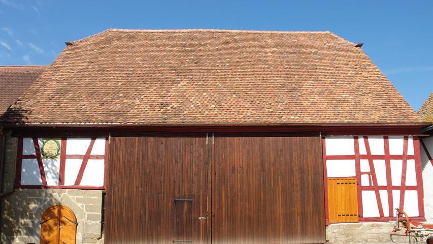 Dem Bewusstsein um die denkmalpflegerische Verantwortung des Eigentümers ist es zu verdanken, dass in Burgbernheim-Buchheim eine zu dem Anwesen Am Schwarzenweg 6 gehörende Scheune erhalten blieb. Der landschaftstypische Sandsteinquaderbau mit Krüppelwalm von 1821 weist hofseitig und am Nordgiebel Fachwerk auf, die westliche Längsseite besteht komplett aus steinsichtigem Sandsteinquadermauerwerk. Den eingeschossigen, großvolumigen Baukörper mit zusätzlicher Lagerfläche in zwei Dachgeschossen und einem Keller kennzeichnet eine annähernd geschlossene Wand- und Dachfläche, die nur durch die Scheunentore unterbrochen wird.
