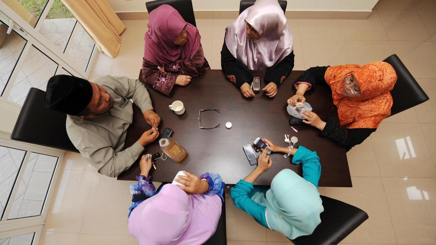 Hier sitzt ein Mann im malaysischen Kuala Lumpur mit mehreren Ehefrauen an einem Tisch. Solche Vielehen können unter Umständen auch in Deutschland weitergeführt werden.