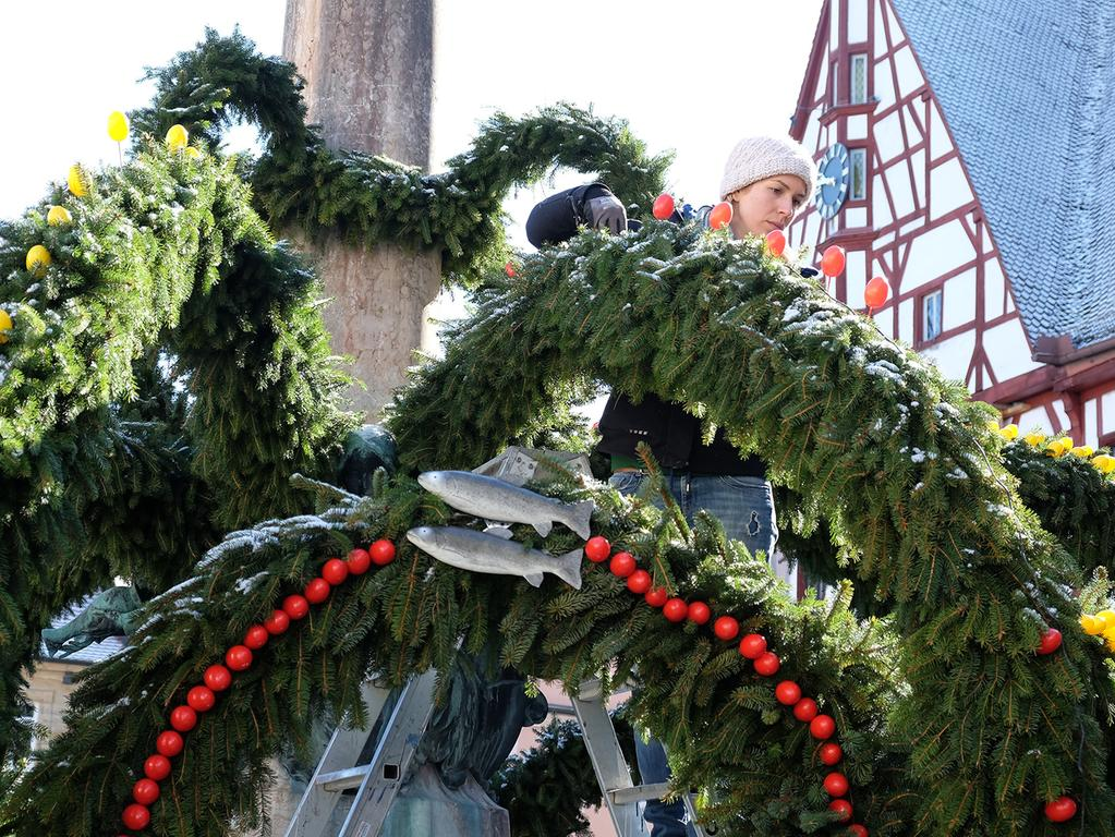 Die Touristenführer und Mitarbeiter des Gartenbauamtes der Stadt Forchheim schmücken den Brunne am Rthausplatz mit gelben und roten Plastikeiern sowie Schleifen. Ein traditioneller Brauch zur Osterzeit; Ostern; Osterbrunnen..Foto: (c) RALF RÖDEL / NN (21.03.2018)