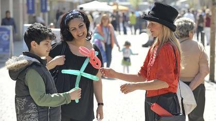In der Fußgängerzone knotet eine Gauklerin bunte Figuren aus Luftballons. Das Publikum nimmt die Kreationen gerne entgegen. Mit solchen Aktionen steigert der Handel den Unterhaltungswert des Einkaufsbummels.