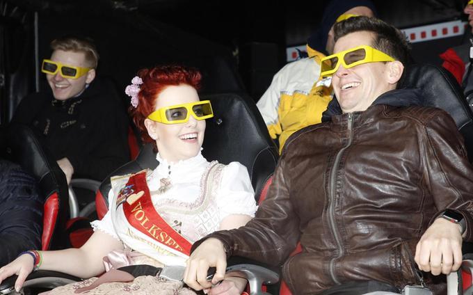 """An der Seite von Radio-N1-Moderator Flo Kerschner, der diesmal auch für einen launigen Bieranstich sorgen soll, testet Volksfestkönigin Carina Kremer die neue Erlebnisbahn """"Laser-Pix"""" (li.) und mit cooler Brille das """"7D-Kino"""" (re.)."""