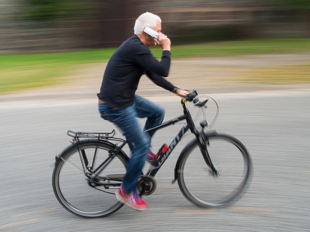 ARCHIV - ILLUSTRATION - Ein Radfahrer telefoniert am 06.10.2015 mit seinem Handy beim Fahren auf einer Straße in Sieversdorf (Brandenburg). Foto: Patrick Pleul/dpa (zu dpa «Online auf dem Rad - Unfallkasse rechnet mit mehr Verletzten» vom 18.05.2016) +++(c) dpa - Bildfunk+++ | Verwendung weltweit