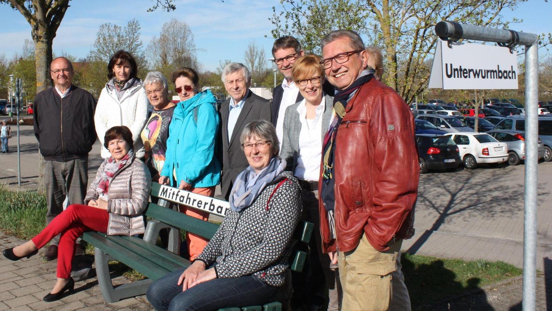 Anita Ermer (sitzend rechts) hat es schon ausprobiert: Das Mitfahrerbänkchen in der Oettinger Straße. Bürgermeister Karl-Heinz Fitz (3. von rechts) und der Vorsitzende des Seniorenbeirats Werner Seifert (links) stellten das Projekt vor. Gut zu erkennen ist Schild, das anzeigt, wohin man fahren möchte.
