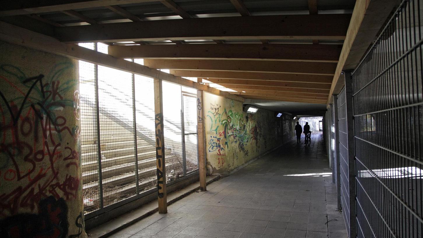 """Balken, Gitter, Zäune: Die Unterführung am ehemaligen Bahnhof Märzfeld ist seit Jahren in einem jämmerlichen Zustand. Der Tunnel soll Teil eines Konzeptes werden, das sich """"Erinnerungsräume"""" nennt."""