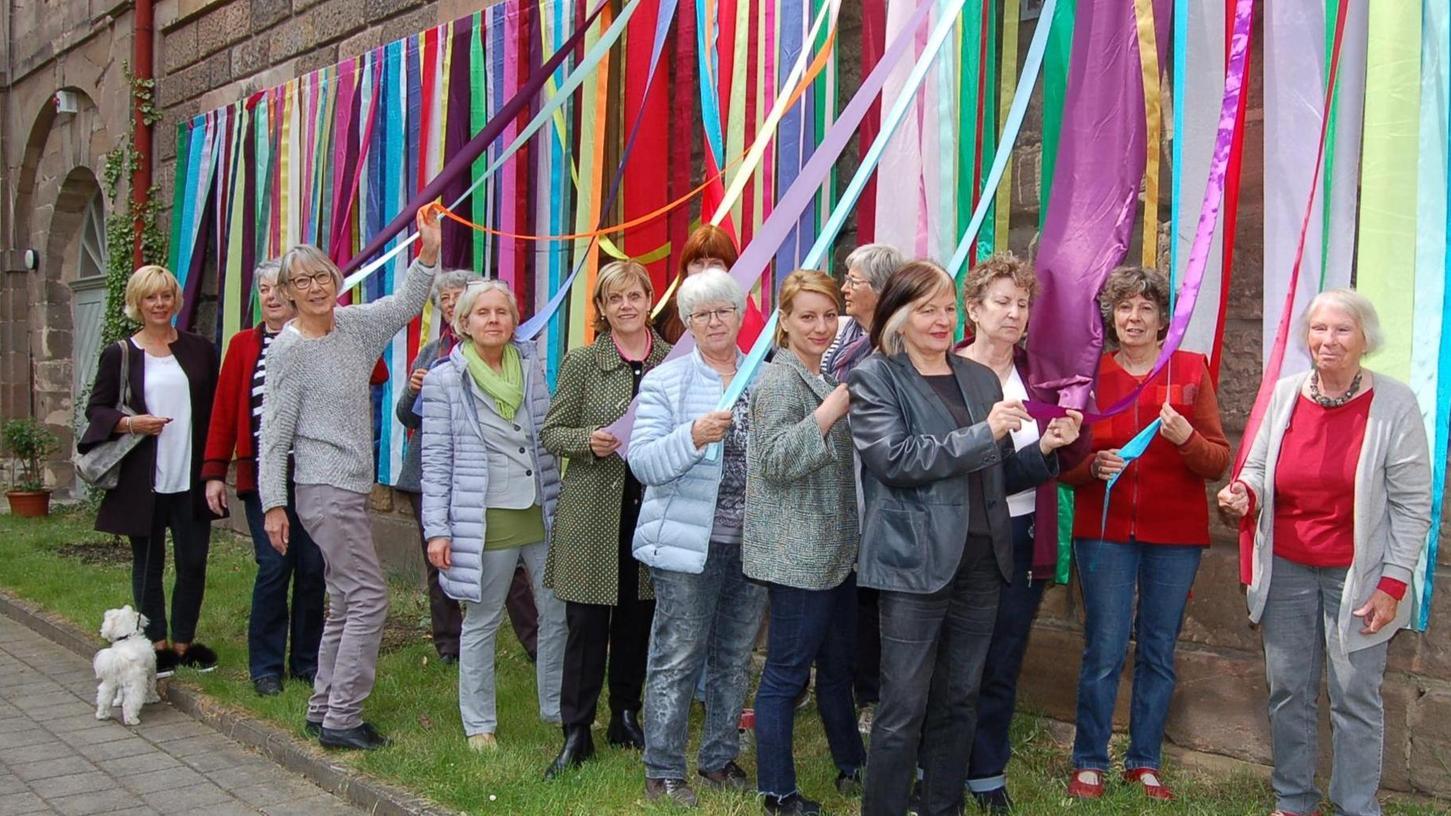 """Bunter Marstall: Das Organisationsteam vor einem Werk der Fürther Künstlerin Barbara Engelhard mit dem Titel """"Ein Gewand für die Wand""""."""