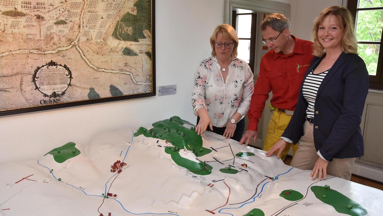 """Einen Überblick über das Schlachtgeschehen an der """"Alten Veste"""" verschafft sich das Kuratorenteam am Modell im Museum Zirndorf (von links): Christine Gottschalk, Thomas Liebert und Nicola Kemmer."""