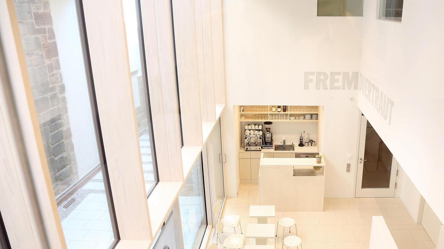 Hell, luftig, einladend: Blick vom ersten Obergeschoss auf Eingangsbereich und Café. Über der Tür zu sehen ist eine Installation der Nürnberger Wort-Künstlerin Dagmar Buhr.