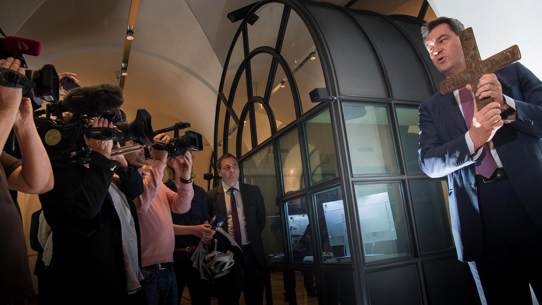 Der Kreuz-Erlass von Ministerpräsident Markus Söder — hier hängt er ein Kreuz demonstrativ in der Staatskanzlei auf — beschäftigt mittlerweile auch Oberbürgermeister Maly und die grüne Fraktion im Stadtrat.