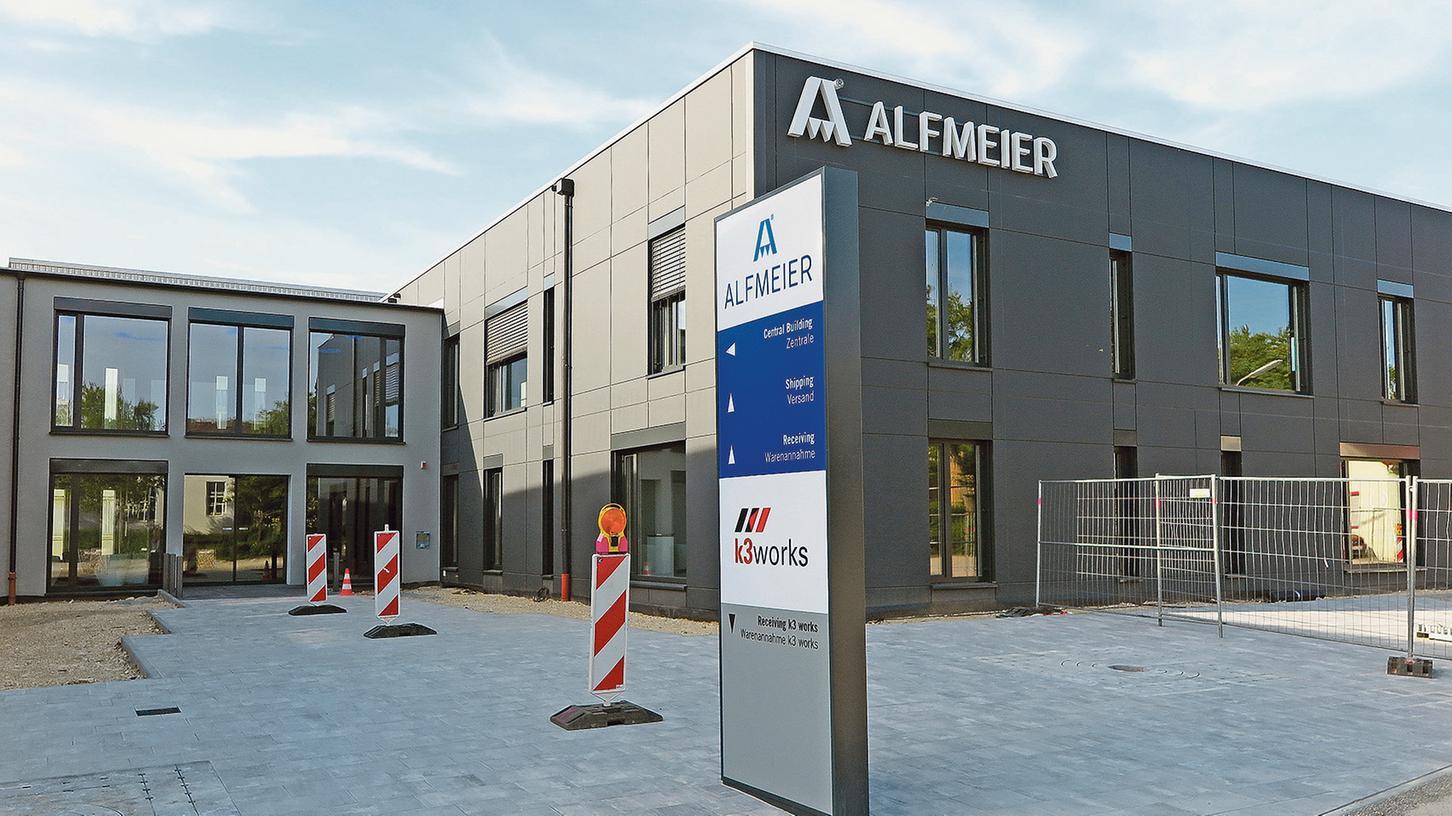 Mit ihrer dunkelgrauen Fassade und strengen Form sticht die neue Alfmeier-Verwaltung in der Industriestraße ins Auge. Bald werden auch die letzten Bauzäune und Warnbaken verschwunden sein.