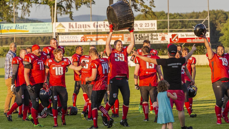 Es ist noch keine Meisterschale, die Ralf Gambel in die Höhe reckt, sondern nur ein Wasserbottich – aber der Anfang ist gemacht: Die Hemhofen Gechers starten mit einem Sieg in ihre American-Football-Karriere.