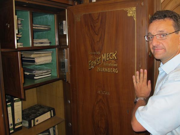 Ein glücklicher Archivar Martin Schramm vor einem geöffneten Tresor.