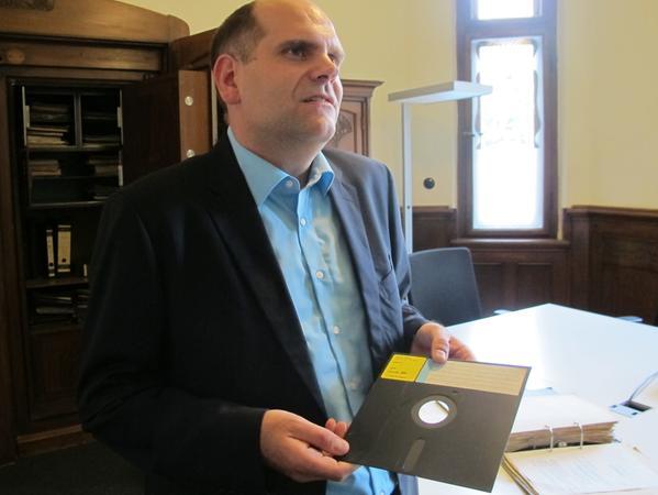 Silbury-Chef Markus Neubauer mit einer rund 40 Jahre alten 8-Zoll-Diskette, im Hintergrund der Tresor.