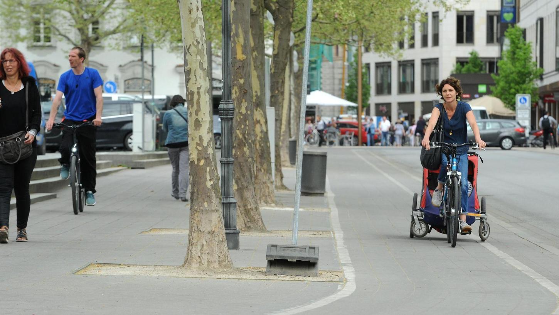 Links und rechts der Bäume an der Rudolf-Breitscheid-Straße, begrenzt von den Stufen auf der einen Seite und den Buden auf der anderen, sollen künftig die beiden Radspuren verlaufen.